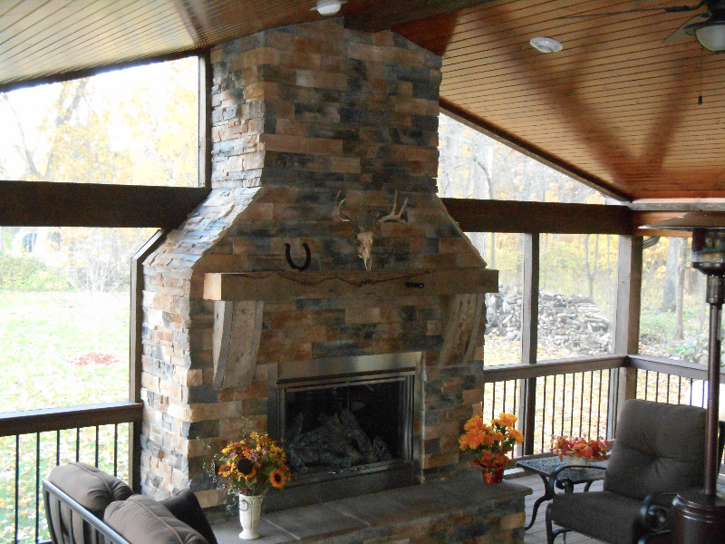 Interior view of Screen Room with stone fireplace & knotty pine ceiling